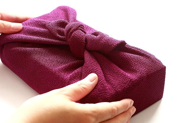 紫の風呂敷に入ったプレゼントを渡す女性